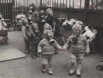 Children in Liverpool playing while wearing gas-masks and protective clothing; Source: The Liverpool Echo